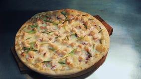 Mani della donna e dell'uomo che dispongono pizza sul piatto di legno sopra lo scrittorio del metallo nella cucina archivi video