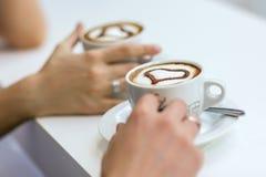Mani della donna e dell'uomo con gli anelli di espousal, tazze di caffè Immagini Stock