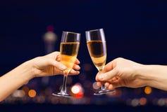 Mani della donna e dell'uomo con i vetri pieni del champagne Fotografie Stock
