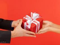 Mani della donna e dell'uomo con il contenitore di regalo Fotografia Stock