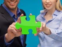 Mani della donna e dell'uomo con il puzzle verde Fotografia Stock Libera da Diritti