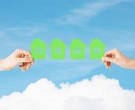 Mani della donna e dell'uomo con molte case del Libro Verde Fotografia Stock Libera da Diritti