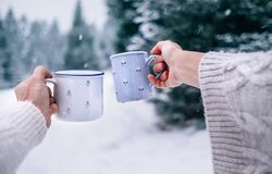 Mani della donna e dell'uomo nel tricottare i guanti che prendono le tazze della bevanda calda fotografia stock
