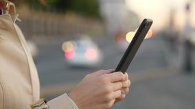Mani della donna facendo uso della fine dello smartphone su contro la strada di sera ed i fari delle automobili stock footage