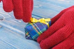 Mani della donna in guanti che disimballano regalo per il Natale o l'altra celebrazione Immagine Stock