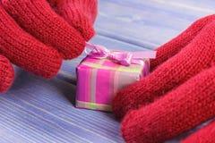 Mani della donna in guanti che disimballano regalo per il Natale o l'altra celebrazione Immagini Stock Libere da Diritti
