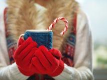 Mani della donna in guanti rossi di lana che tengono una tazza accogliente con cacao caldo, tè o caffè e un bastoncino di zuccher Immagini Stock Libere da Diritti