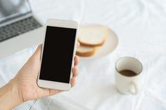 Mani della donna lavoratrice che tengono e che per mezzo dello Smart Phone sul fondo dello scrittorio Sullo scrittorio abbia il c fotografie stock
