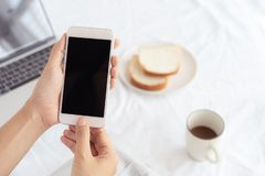 Mani della donna lavoratrice che tengono e che per mezzo dello Smart Phone sul fondo dello scrittorio Sullo scrittorio abbia il c immagine stock