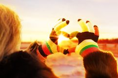 Mani della donna nei guanti di inverno backlit dall'incandescenza calda del sole Fotografie Stock Libere da Diritti