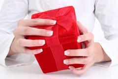Mani della donna sul contenitore di regalo rosso del velluto Immagini Stock Libere da Diritti