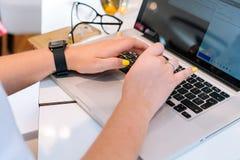 Mani della donna unrecognisable che si siedono nell'ufficio che coworking e che scrive sul suo computer della tastiera del comput fotografia stock