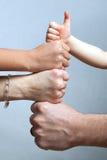 Mani della famiglia con i pollici in su Immagine Stock