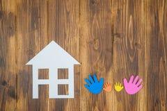 Mani della famiglia con la casa di carta Immagine Stock