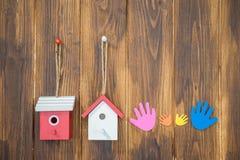 Mani della famiglia con la casa di modello Immagine Stock
