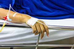 Mani della gente cari malati che si trovano su un letto nell'ospedale Fotografie Stock