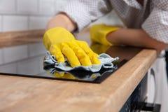 Mani della giovane donna che puliscono una fresa nera moderna di induzione da uno straccio, lavoro domestico immagini stock