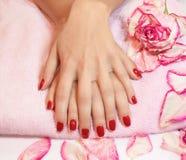 Mani della giovane donna con il manicure rosso Immagini Stock Libere da Diritti