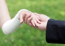 Mani della holding della sposa e dello sposo esterni Fotografia Stock