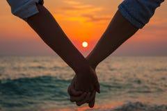 Mani della holding delle coppie al tramonto del mare Immagine Stock