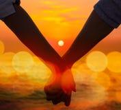 Mani della holding delle coppie al tramonto del mare Fotografie Stock