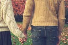 Mani della holding delle coppie in sosta Fotografia Stock