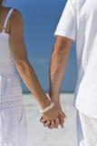 Mani della holding delle coppie su una spiaggia vuota Fotografie Stock