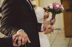 Mani della holding dello sposo e della sposa Immagini Stock
