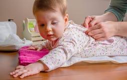 Mani della madre che indossano suo riposarsi del bambino Fotografia Stock