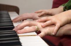 Mani della madre e del bambino dal piano che plaing Fotografie Stock