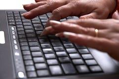 Mani della metà di donna di età sul computer portatile immagine stock