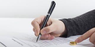Mani della moglie, sentenza di divorzio di firma del marito, dissoluzione, annullante matrimonio, documenti di separazione legale fotografia stock