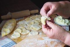 Mani della nonna a cucinare vareniki con la ricotta Immagine Stock Libera da Diritti