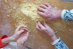 Mani della nonna e del nipote alla cottura Immagini Stock Libere da Diritti