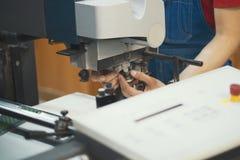 Mani della persona che funzionano con le apparecchiature di stampa del macchinario immagine stock