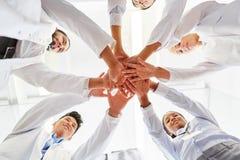 Mani della pila degli studenti insieme per lo spirito di gruppo Immagini Stock