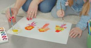 Mani della pittura della figlia e della madre sul pavimento video d archivio