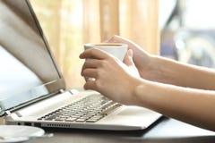 Mani della ragazza con il computer portatile di sorveglianza del caffè Fotografie Stock Libere da Diritti