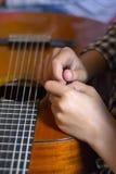 Mani della ragazza e della chitarra acustica fotografia stock libera da diritti