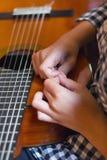 Mani della ragazza e della chitarra acustica immagini stock