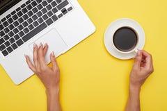 Mani della ragazza facendo uso del touchpad e della tazza di caffè di tenuta Fotografia Stock Libera da Diritti