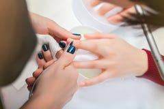 Mani della ragazza nei bagni con acqua durante il manicure, pulenti la cuticola Immagine Stock Libera da Diritti