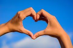 Mani della ragazza nella forma del cuore di amore su cielo blu Fotografie Stock Libere da Diritti