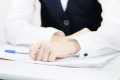 Mani della scolara in uniforme con la penna ed il quaderno Fotografie Stock Libere da Diritti