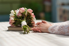 Mani della sposa con l'anello il suo dito sulla tavola Fotografie Stock