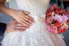 Mani dello sposo e della sposa con le fedi nuziali e un for Disegni del mazzo sul basamento degli scioperi