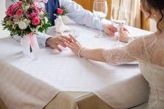 Mani della sposa e dello sposo con le fedi nuziali sulla tavola con il mazzo dei fiori di nozze Fotografia Stock