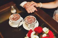 Mani della sposa e dello sposo sulla tavola, tazze di caffè del latte Immagini Stock Libere da Diritti