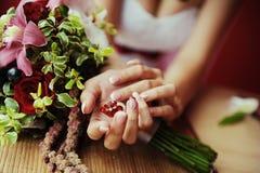 Mani della sposa su un fondo di un mazzo di nozze Fotografia Stock