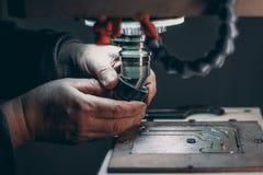 Mani della taglierina cambiante del lavoratore in fresatrice di CNC Immagine Stock